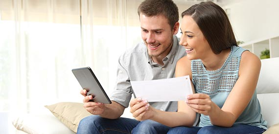Woman and man sitting on a couch together smiling while man holds tablet and woman holds paper.
