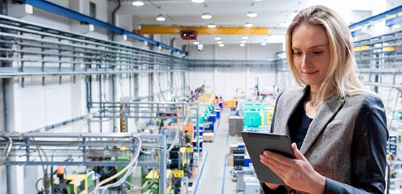 Woman in business attire looking down at tablet in a factory.